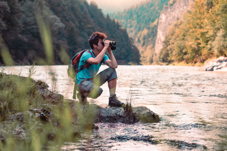 Young tourist with backpack looks through a binoculars on mountains peaks, stands on a rock over a river. Boy spends a vacation in mountains, wandering with backpack, he is wearing sports summer clothes