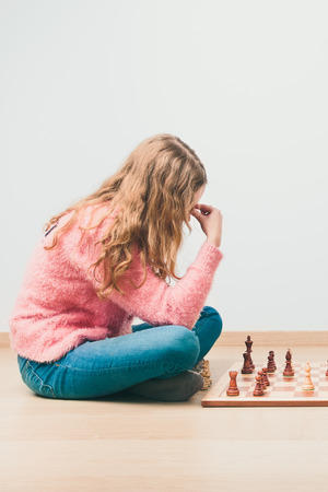Girl deeply thinking about next move during chess game. Copy space for text at the top and bottom of image