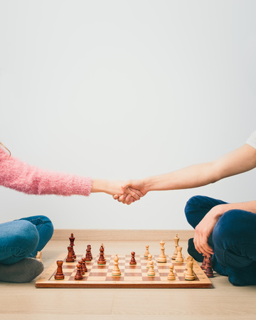 Chess game is over. Girl and boy handshaking after finished chess game, thanking for playing. Copy space for text at the top of image