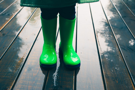 Closeup of legs of kid standing on a porch wearing green wellies and raincoat. Rain boots in bright green color Stock Photo