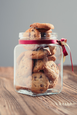 Big jar filled with oat cookies standing on a wooden table. Plain background. Portrait orientation