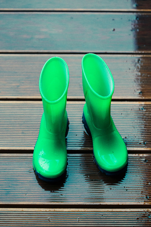 Blue wellies standing on a wooden porch while raining Stock Photo