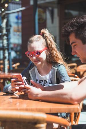 Young woman and man sitting in pavement cafe a the table talking and using mobile phones