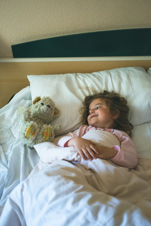 Little girl lying in a bed with teddy bear at the morning Reklamní fotografie - 123622652