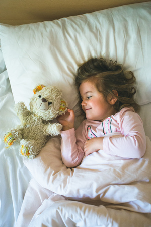 Little girl lying in a bed with teddy bear at the morning Reklamní fotografie - 123622654