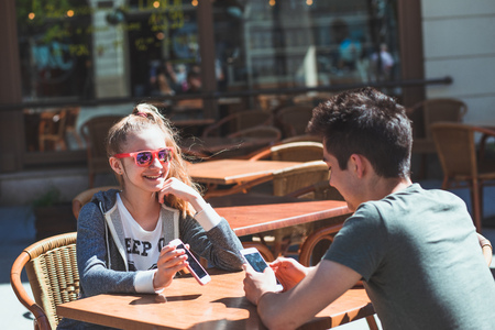 Young woman and man sitting in pavement cafe a the table talking and using mobile phones Reklamní fotografie - 123622655