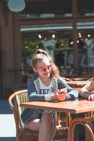 Young woman and man sitting in pavement cafe a the table talking and using mobile phones Reklamní fotografie - 123622658