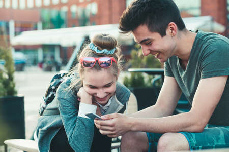 Couple of friends, teenage girl and boy, having fun with smartphones, sitting in center of town, spending time together