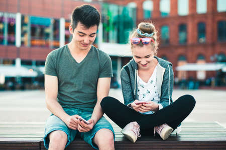 Couple of friends, teenage girl and boy, having fun together with smartphones, sitting in center of town, spending time together