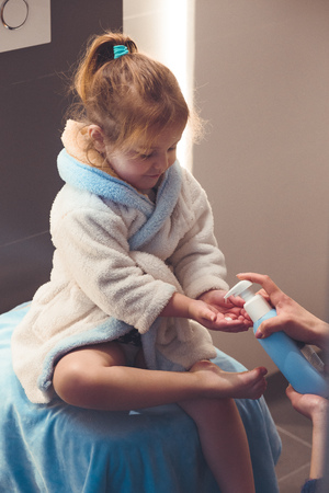 Mother applying moisturizing cream on her daughter's legs after bath. Mom caring about her child. Girl sitting in bathroom, wearing bathrobe Reklamní fotografie - 123610838