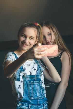 Young women taking selfie, using smartphone camera. Girls making faces, enjoying taking funny pictures together Reklamní fotografie - 123610841