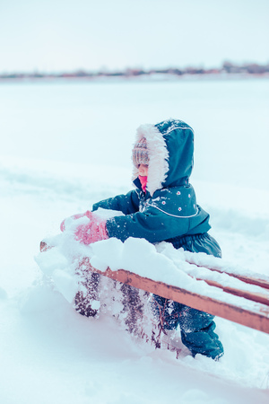 Little girl enjoying winter removing snow from a bench. Toddler is playing outdoors while after snowfall. Child is wearing dark blue snowsuit and wool cap Reklamní fotografie - 123610845