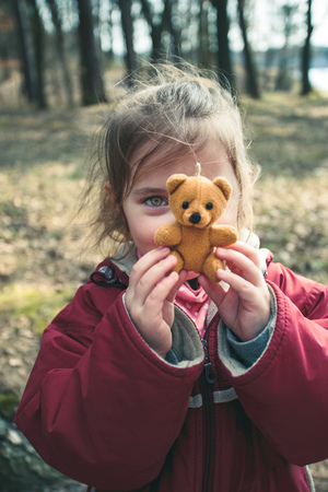 Little smilling happy girl playing with her little teddy bear toy in a park on sunny spring day. Child holding teddy at front of face looking at camera wearing red jacket Reklamní fotografie