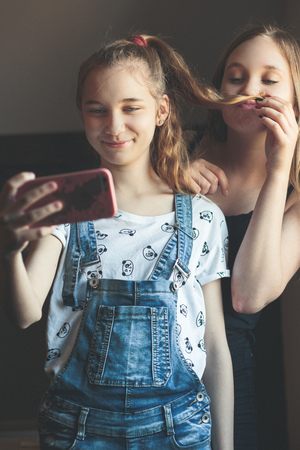 Young women taking selfie, using smartphone camera. Girls making faces, enjoying taking funny pictures together Reklamní fotografie - 123610844