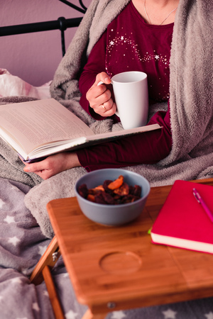 Woman enjoying the reading a book and drinking coffee at home. Young woman sitting in bed, wrapped in blanket, holding book, relaxing at home. Candid people, real moments, authentic situations Reklamní fotografie