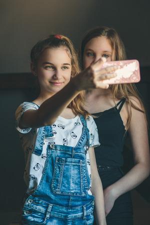 Young women taking selfie, using smartphone camera. Girls making faces, enjoying taking funny pictures together Reklamní fotografie