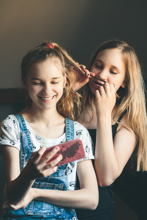 Young women taking selfie, using smartphone camera. Girls making faces, enjoying taking funny pictures together Reklamní fotografie - 123622722