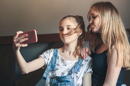 Young women taking selfie, using smartphone camera. Girls making faces, enjoying taking funny pictures together Reklamní fotografie - 123622721