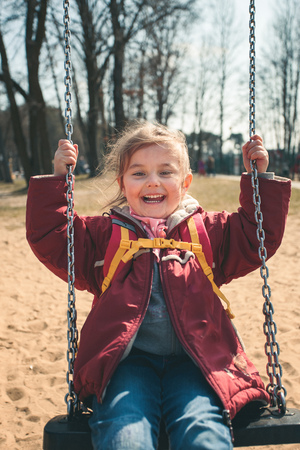 Little smilling happy girl swinging in a park on sunny spring day. Child looking at camera wearing red jacket Reklamní fotografie