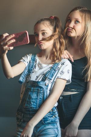 Young women taking selfie, using smartphone camera. Girls making faces, enjoying taking funny pictures together Reklamní fotografie - 123622720