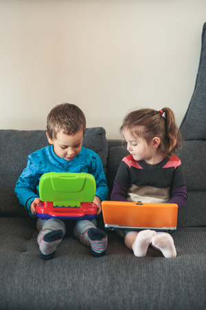 Two children playing with laptops learning basic digits, characters, sounds and images. Little girl and boy sitting on sofa and playing together at home. Candid people, real moments, authentic situations