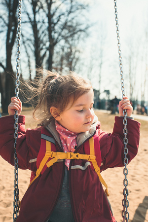 Little cute girl swinging in a park on sunny spring day. Child wearing red jacket Reklamní fotografie - 123622730
