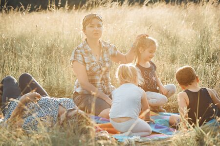 Family spending time together on a meadow, close to nature. Parents and children sitting and playing on a blanket on grass. Candid people, real moments, authentic situations Standard-Bild