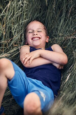 Little happy smiling boy playing in a tall grass in the countryside. Candid people, real moments, authentic situations Reklamní fotografie