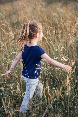 Little happy girl walking through a tall grass in the countryside. Candid people, real moments, authentic situations