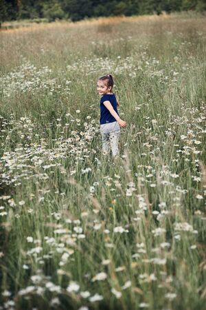Little happy girl playing in a tall grass in the countryside. Candid people, real moments, authentic situations