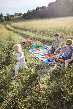Family spending time together on a meadow, close to nature, roasting marshmallows over a campfire, parents and children sitting on a blanket on grass. Candid people, real moments, authentic situations