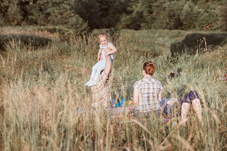 Family spending time together on a meadow, close to nature. Parents and children sitting and playing on a blanket on grass. Candid people, real moments, authentic situations Reklamní fotografie