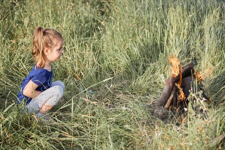Little girl looking at campfire sitting in a grass. Candid people, real moments, authentic situations