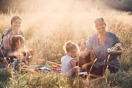 Family spending time together on a meadow, close to nature, parents and children playing together, making coronet of wild flowers. Candid people, real moments, authentic situations