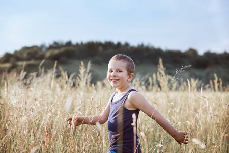 Little happy boy walking through a tall grass in the countryside. Candid people, real moments, authentic situations
