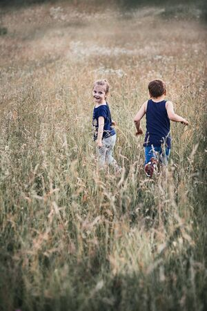 Little happy kids playing in a tall grass in the countryside. Candid people, real moments, authentic situations