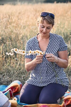 Smiling happy woman making coronet of wild flowers. Family spending time together on a meadow, close to nature. Candid people, real moments, authentic situations