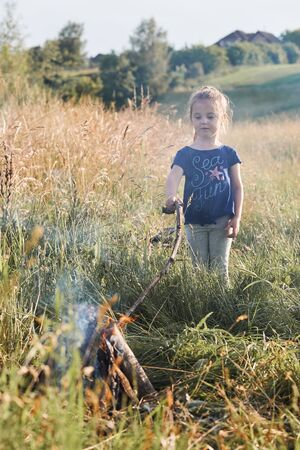 Little girl roasting marshmallow over a campfire on a meadow. Candid people, real moments, authentic situations