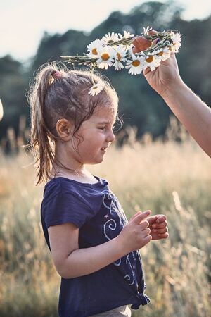 Mother putting a coronet of wild flowers on a head of little girl. Family spending time together on a meadow, close to nature. Parents and children playing together. Candid people, real moments, authentic situations