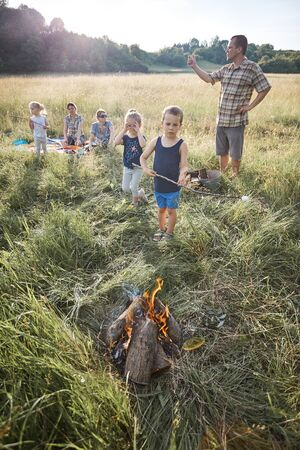 Little boy roasting marshmallow over a campfire. Family spending time together on a meadow, close to nature. Parents and children sitting on a blanket on grass. Candid people, real moments, authentic situations