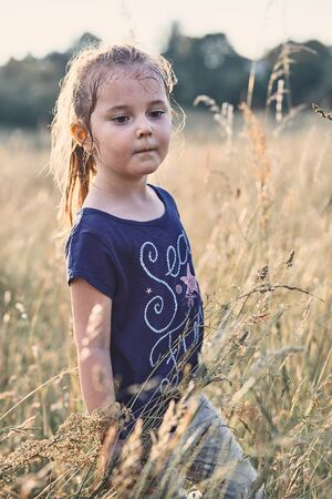 Little happy smiling girl playing in a tall grass in the countryside. Candid people, real moments, authentic situations Reklamní fotografie