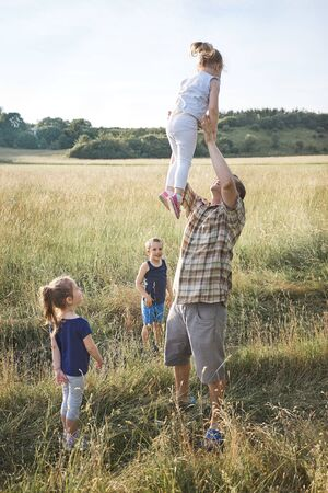 Father tossing little girl in the air. Family spending time together on a meadow, close to nature. Parents and children playing together. Candid people, real moments, authentic situations