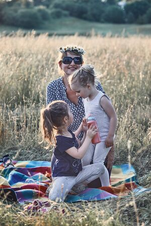Family spending time together on a meadow, close to nature. Parents and children playing together, making coronet of wild flowers. Candid people, real moments, authentic situations