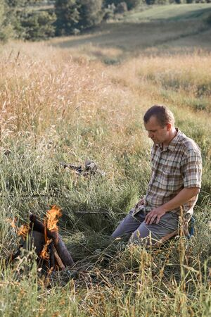 Man sitting in a grass beside a campfire on a meadow. Candid people, real moments, authentic situations