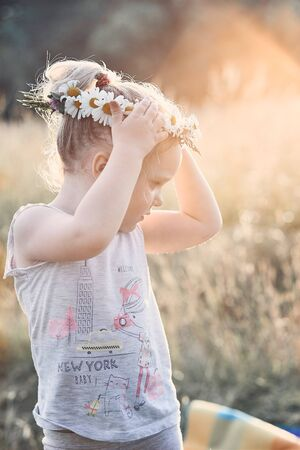 Little girl wearing a coronet of wild flowers on her head. Candid people, real moments, authentic situations Reklamní fotografie