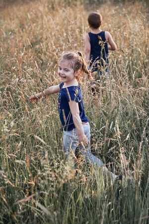 Little happy smiling kids playing in a tall grass in the countryside. Candid people, real moments, authentic situations Reklamní fotografie