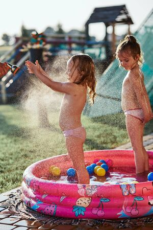 Little cute adorable girls enjoying a cool water sprayed by their father during hot summer day in backyard. Candid people, real moments, authentic situations Reklamní fotografie