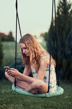 Young woman using mobile phone smartphone sitting on swing in a backyard