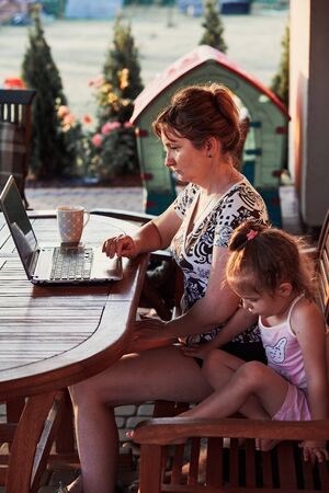 Mother working at home, using portable computer, sitting on patio with her daughter on summer day
