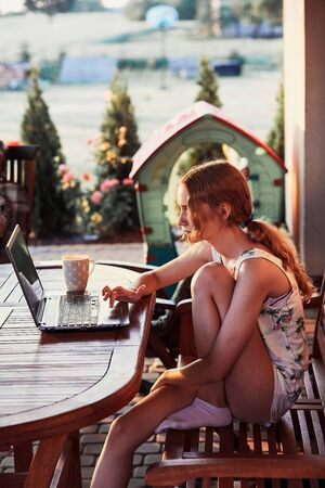Woman working at home, using portable computer, sitting on patio on summer day Reklamní fotografie